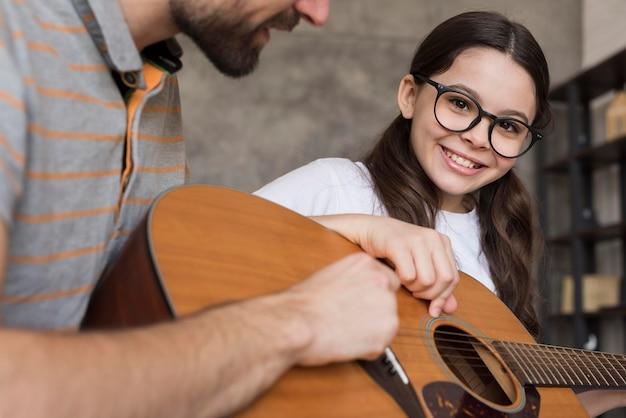 Pai de close-up, ensinando a menina a tocar violão