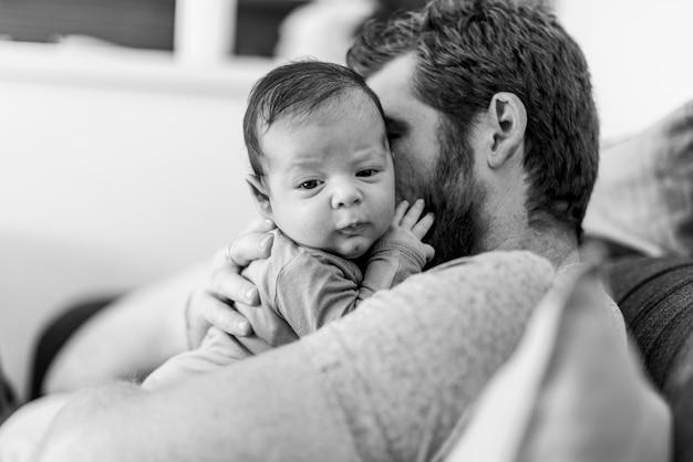 Pai de close-up, segurando o bebê em tons de cinza