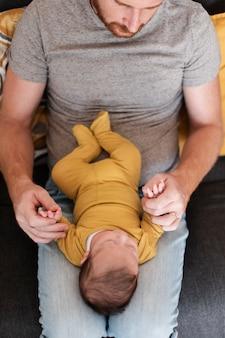 Pai de close-up, segurando o bebê nas pernas