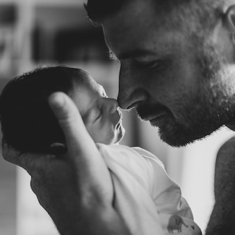 Pai de close-up, tocando o bebê com o nariz
