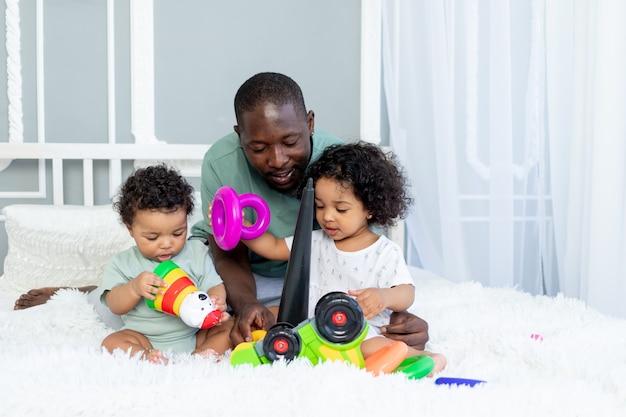 Pai de família afro-americano com crianças, bebês, brincam e colecionam uma pirâmide colorida em casa na cama, família feliz