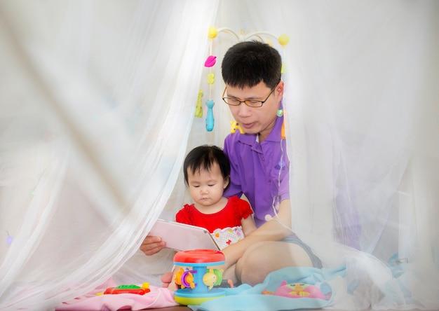 Pai de família feliz e daughterand jogando um tablet digital no quarto em casa