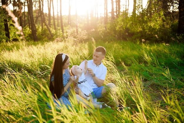 Pai de família feliz, mãe brincando ao ar livre no campo assistindo o belo pôr do sol emocional na luz de fundo
