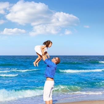 Pai de família segurando a filha jogando praia