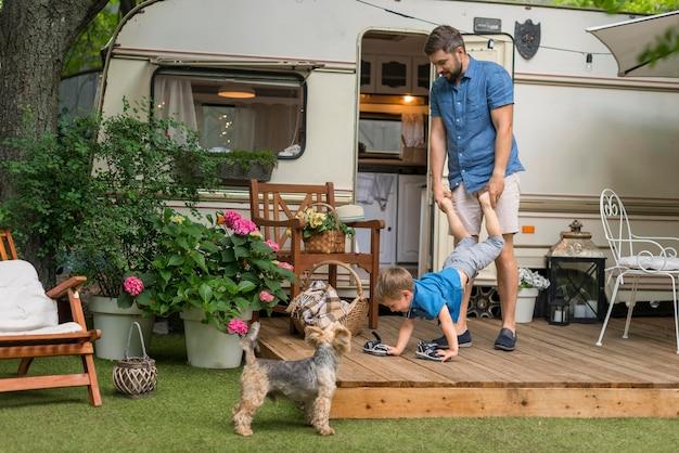 Pai de frente brincando com seu filho ao lado de uma caravana