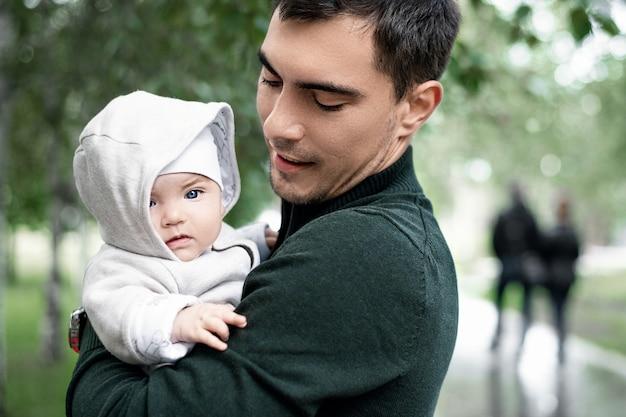 Pai de jaqueta verde com bebê nos braços em caminhada no parque