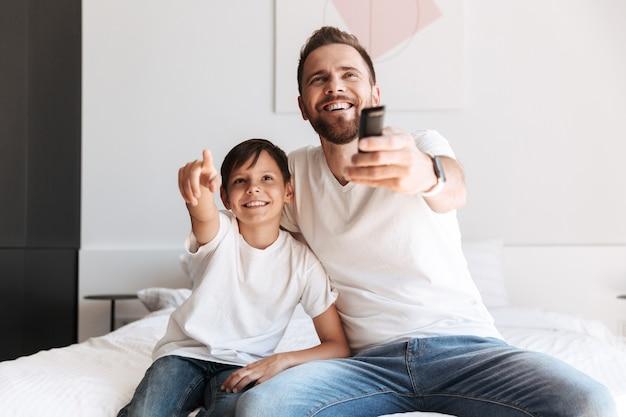 Pai de jovem pai se divertindo com seu filho assistindo tv segurando o controle remoto.