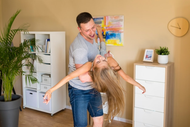 Pai de lado brincando com a filha em casa
