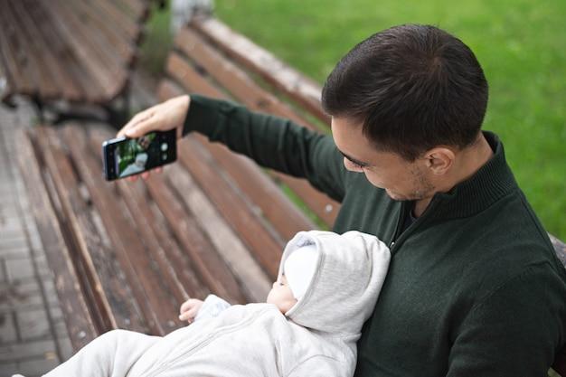 Pai de macacão verde com bebê nos braços, sentado no banco, tirando selfie no smartphone