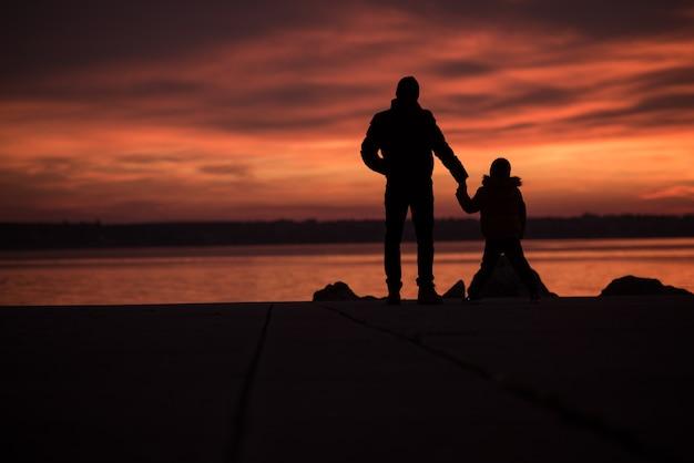 Pai de mãos dadas com o filho enquanto a silhueta deles se destaca contra um pôr do sol laranja intenso no oceano
