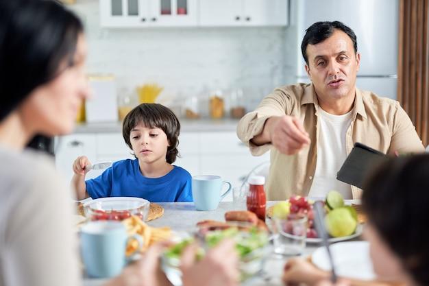 Pai de meia idade conversando com crianças, usando o tablet pc enquanto comia dentro de casa. família latina desfrutando a refeição juntos, sentados à mesa na cozinha em casa. conceito de família feliz