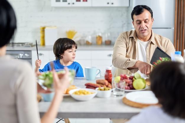 Pai de meia idade conversando com seu filho enquanto toma café da manhã. família latina desfrutando a refeição juntos, sentados à mesa na cozinha em casa. conceito de família feliz