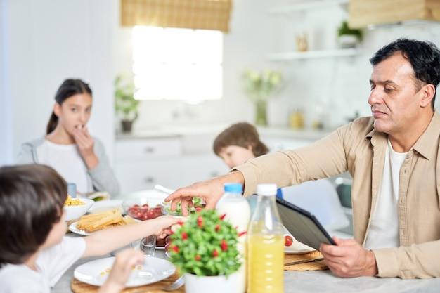 Pai de meia idade desfrutando de uma refeição junto com sua família, usando o tablet digital enquanto está sentado à mesa na cozinha em casa. família feliz, tecnologia, conceito matinal