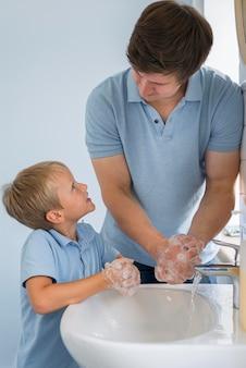 Pai de perto ensinando filho a lavar as mãos