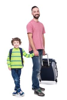 Pai de sorriso novo e seu filho com bagagem.