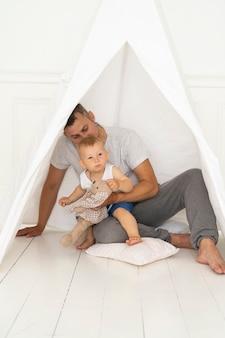 Pai de tiro completo sentado com menino debaixo da tenda