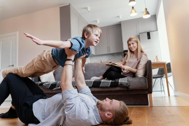 Pai de tiro médio e filho brincando em casa