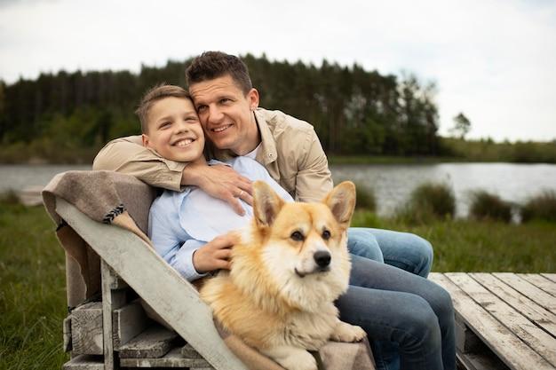 Pai de tiro médio e filho com cachorro