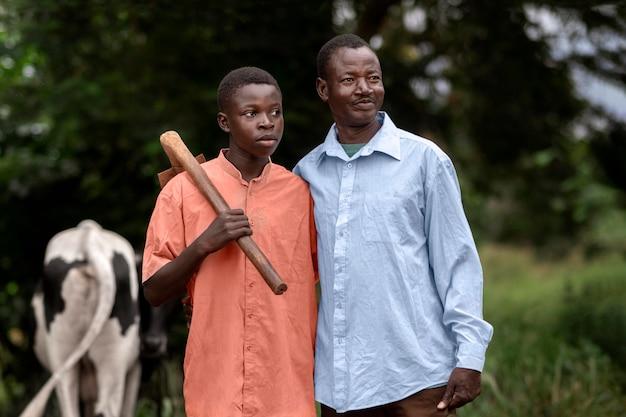Pai de tiro médio e filho com vaca ao ar livre