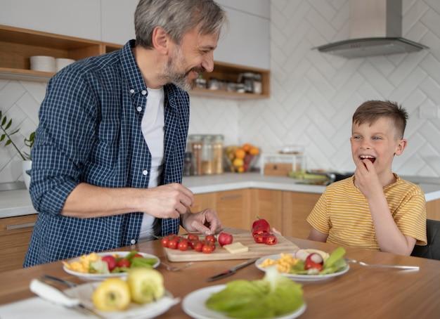 Pai de tiro médio e filho cozinhando