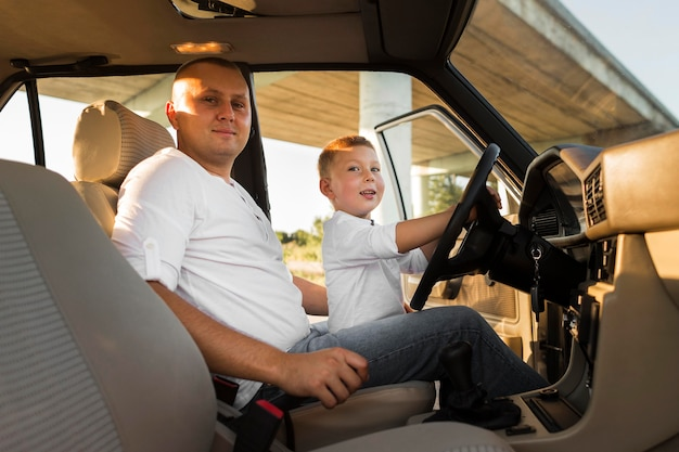 Pai de tiro médio e filho no carro