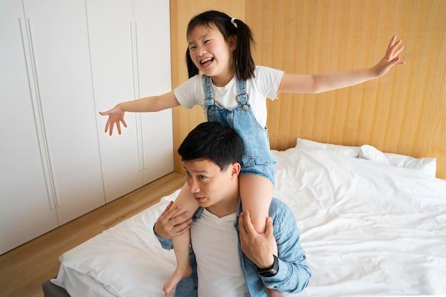 Pai de tiro médio segurando a garota nos ombros