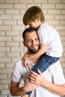Pai de vista frontal, segurando seu filho