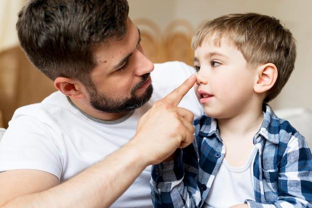Pai de vista frontal tocando seu nariz de filho