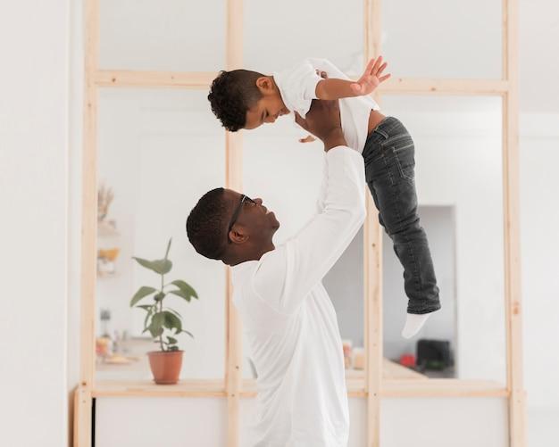 Pai de vista lateral brincando com seu filho dentro de casa