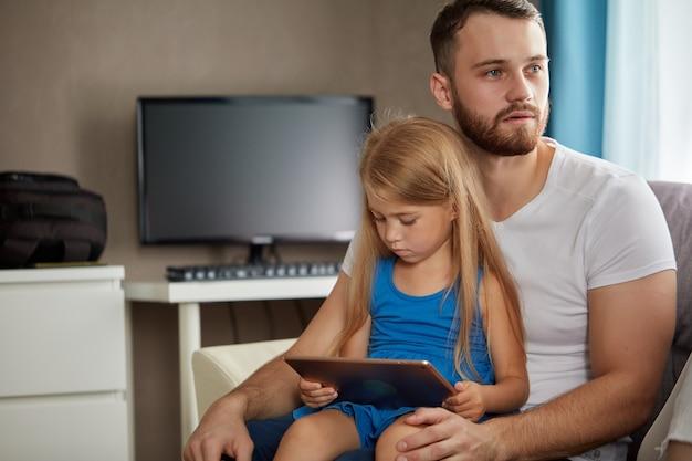 Pai deprimido sentado com filha de joelhos