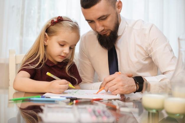 Pai desenhando com a filha na cozinha pela manhã depois de comer, antes de ir para o trabalho.
