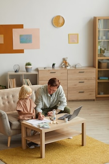 Pai desenhando junto com seu filho pequeno à mesa nos momentos de lazer em casa