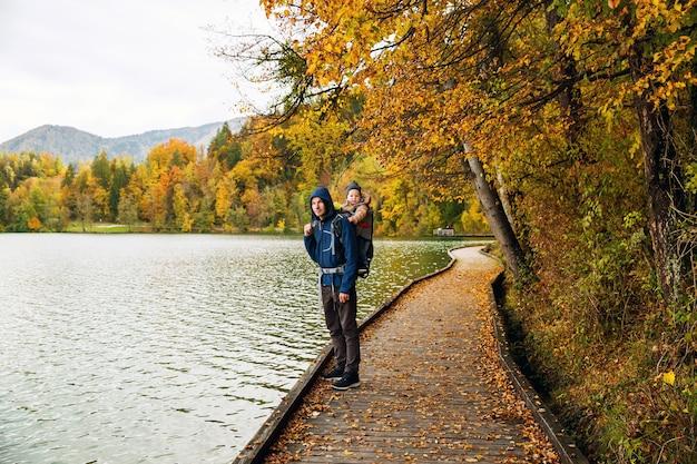 Pai desportivo e filho pequeno caminhando no lago bled na eslovênia, europa