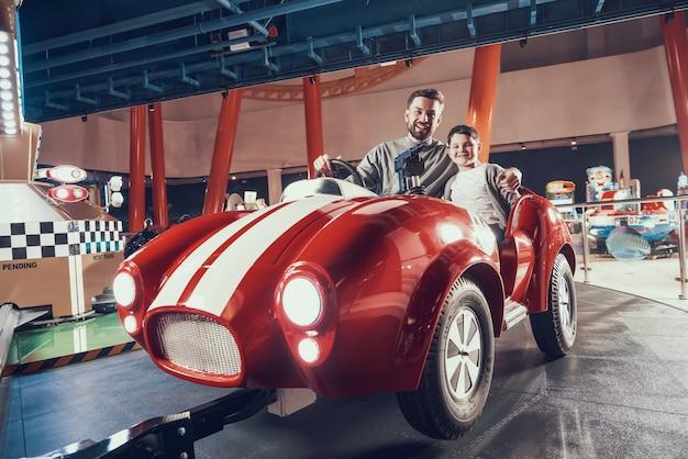 Pai divertido e filho de sorriso que sentam-se no carro do brinquedo.