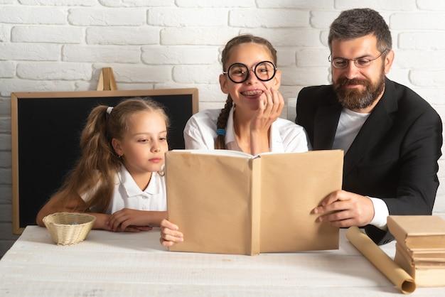 Pai, divirta-se com lindas garotas em idade escolar. pai e filhas pequenas. amo a família, o conceito de infância de paternidade de dia de professores. lendo um livro.