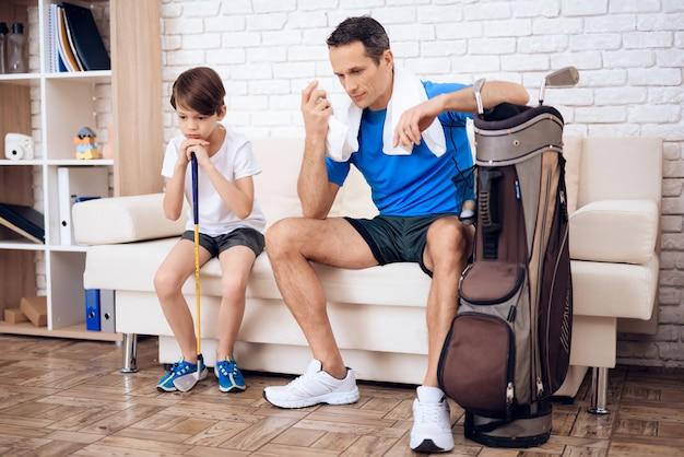Pai diz ao filho sobre golfe.