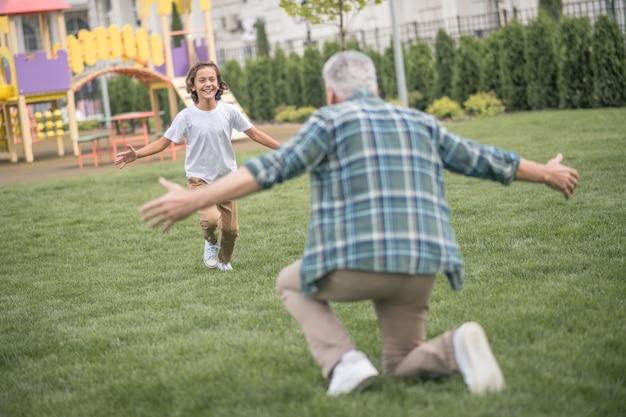 Pai do fim de semana. menino correndo para o pai e parecendo feliz