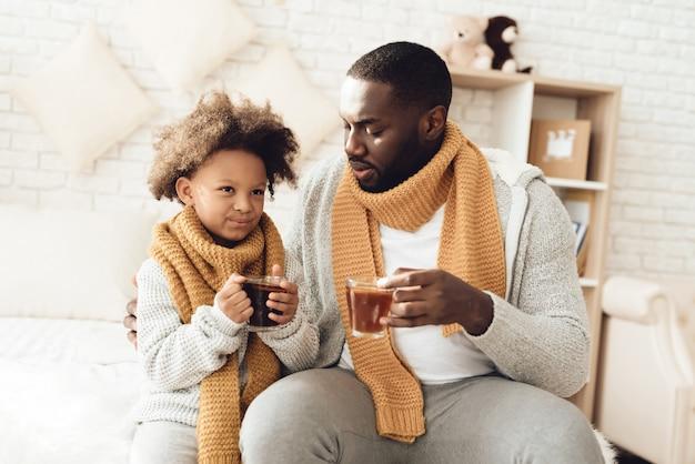 Pai doente e filha bebendo chá sentado na cama em casa