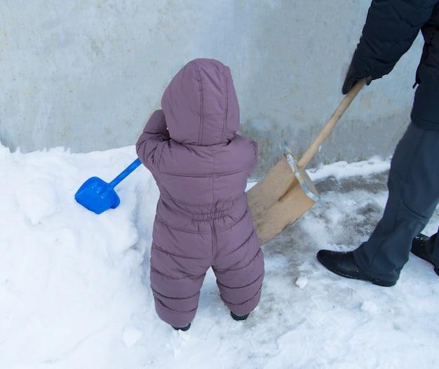 Pai e bebê juntos para limpar as pás de neve