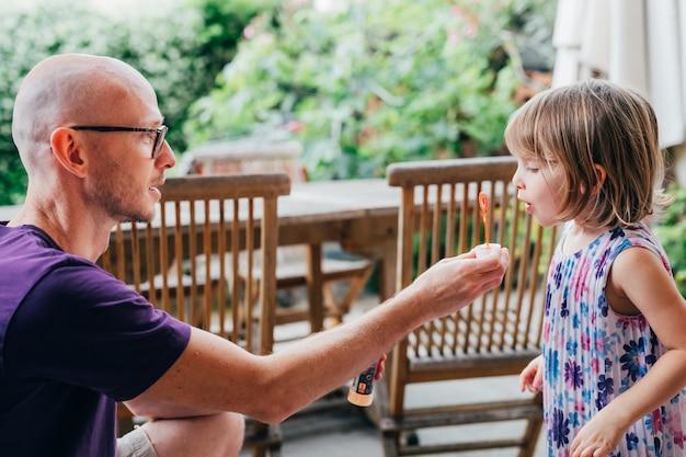 Pai e criança do sexo feminino ao ar livre jogando sabão bolha