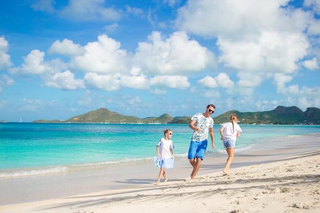 Pai e crianças pequenas que apreciam férias tropicais do verão da praia. família, tocando, praia