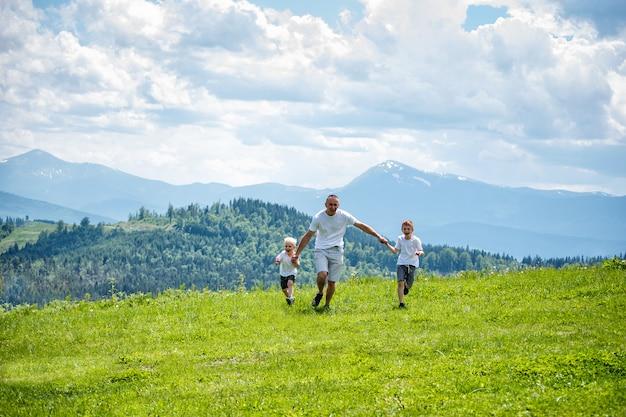 Pai e dois filhos correndo no campo verde, de mãos dadas