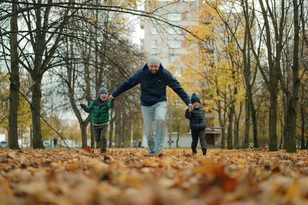 Pai e dois filhos correndo pelo parque de outono de mãos dadas