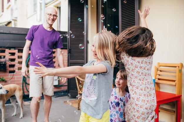 Pai e duas crianças do sexo feminino ao ar livre jogando sabão bolha