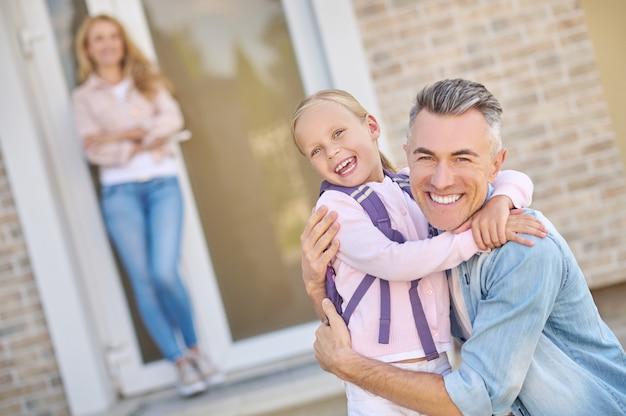Pai e filha alegres se abraçando perto de casa