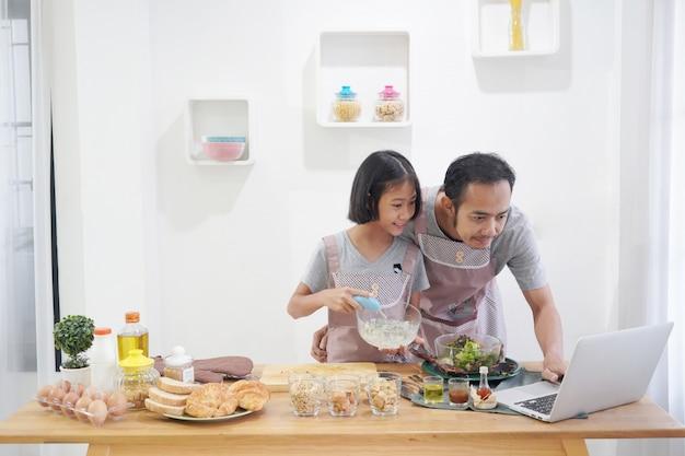 Pai e filha, aprendendo a cozinhar on-line usando o computador portátil na cozinha em casa