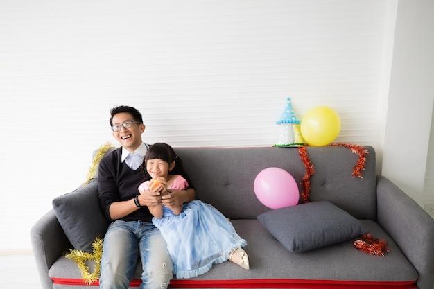 Pai e filha asiáticos relaxando no sofá