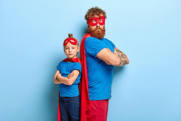 Pai e filha autoconfiantes se distanciam e mantêm os braços cruzados