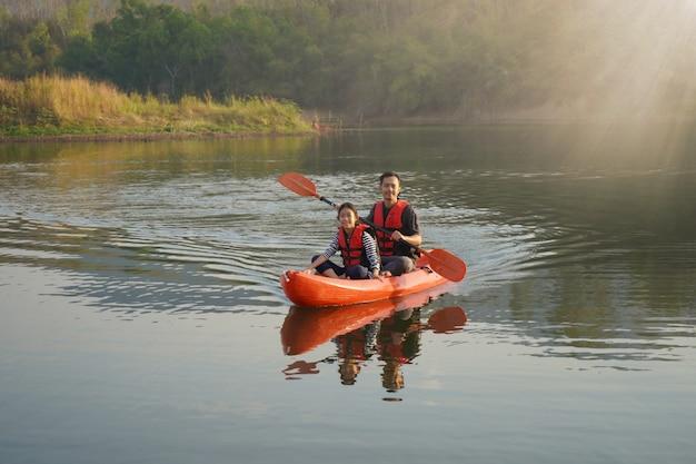 Pai e filha barco a remo em águas calmas