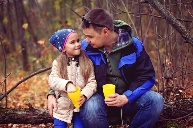 Pai e filha bebendo chá na floresta de outono